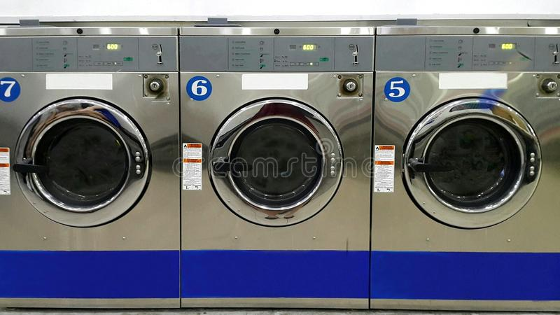 Close up full frame of industrial washing machines for public use in laundromat/ laundrette royalty free stock image