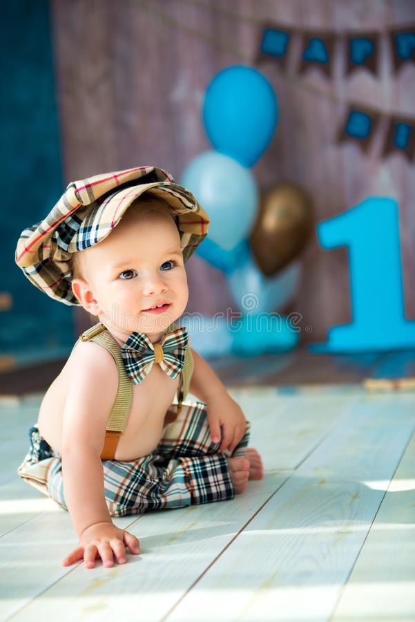 Close-up full-length portrait of a little boy gentleman in a retro suit with suspenders, in a cap and a bow tie. elebration Happy stock images