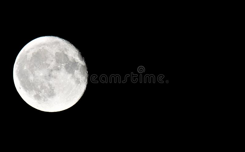 Close up of full moon with black background on left side of photo with copy space royalty free stock images