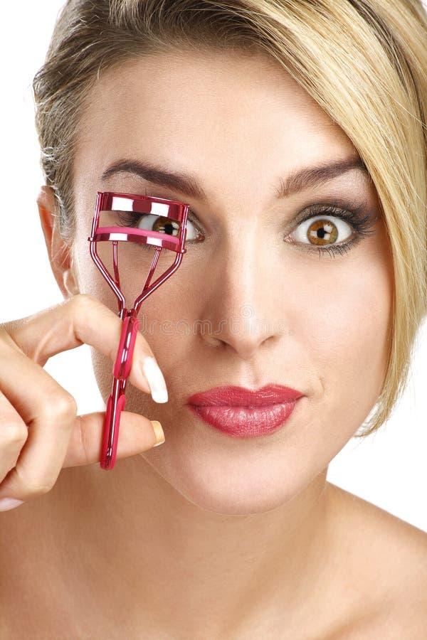 Close up of a funny beautiful girl using eyelash curler stock photos