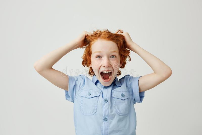 Close up of funny little boy with red hair and freckles pulling hair with hands,screaming with surprised expression. Being super happy new gyroscooter for stock images