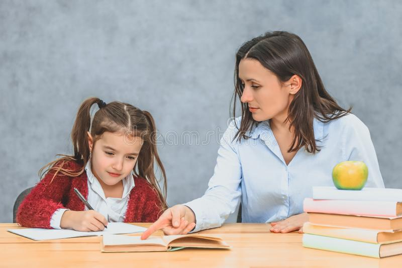 Close up funny mother and child daughter doing homework writing and reading at home. stock photography