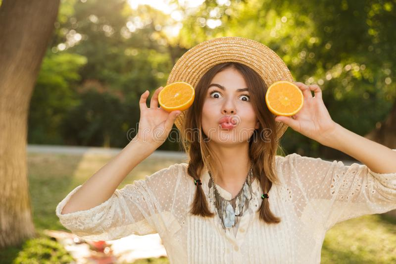 Close up of funny young girl in summer hat spending time at the park, stock image