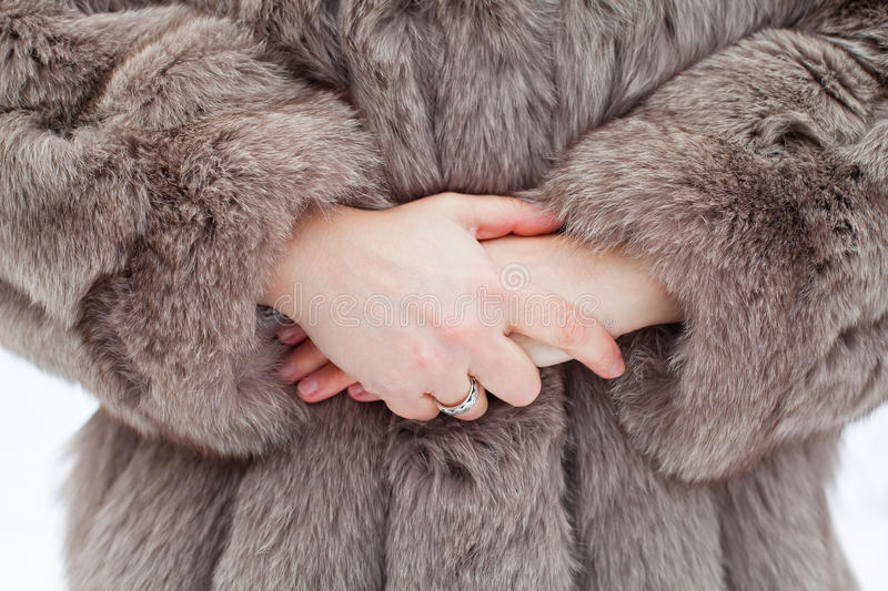 Close up fur coat & female hands royalty free stock photography