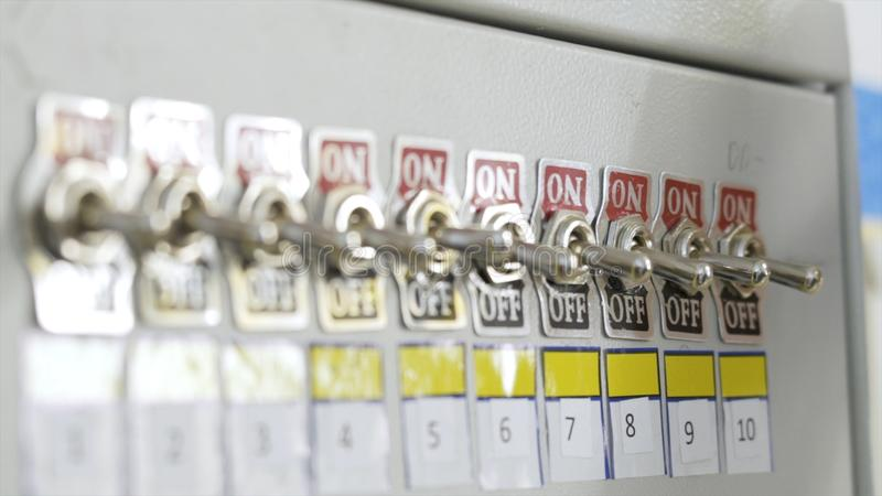 Close-up of fuse switch panel. Action. Manual panel with toggle switches on factory fuse. Hand of factory worker stock image