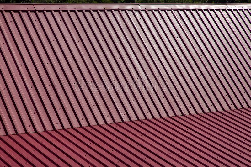 Close-up of gable roof covered. Close-up of the overlapping of a gable roof covered with metal knurled sheets of red color stock photos
