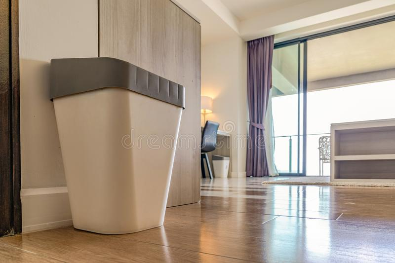 Close up garbage rubbish trash plastic can with gray cover in the resort bedroom with the window light behind royalty free stock images