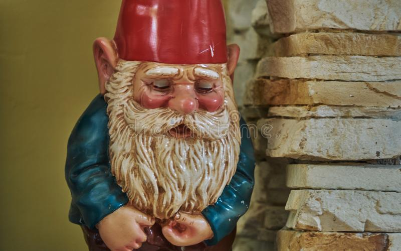 A close-up of a garden gnome with a red hat and white beard. Statue, figurine, face, cute, decoration, green, old, head, handmade, new, tiny, decorated, toy stock image