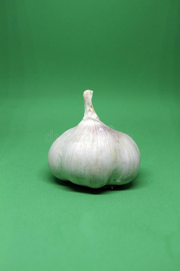 Close-up of garlic clove on green background stock photography