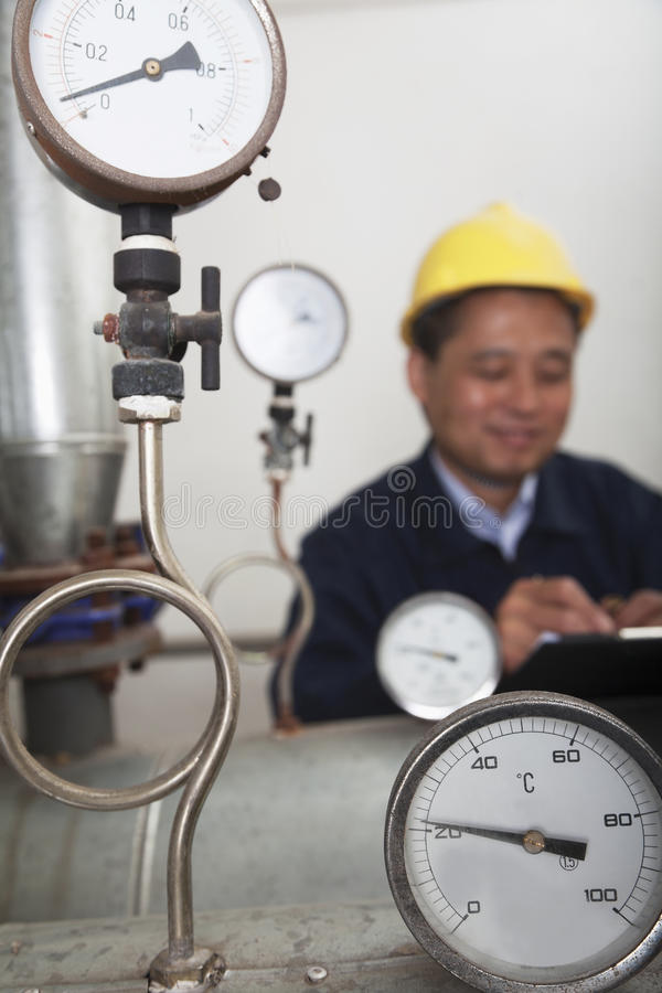 Close- up on gas gauges with worker in the background in a gas plant, Beijing, China stock image