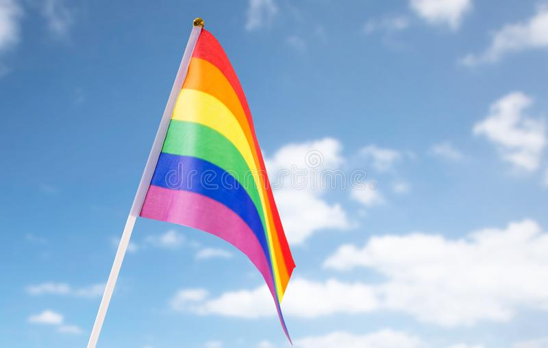 Close up of gay pride rainbow flag over blue sky royalty free stock images