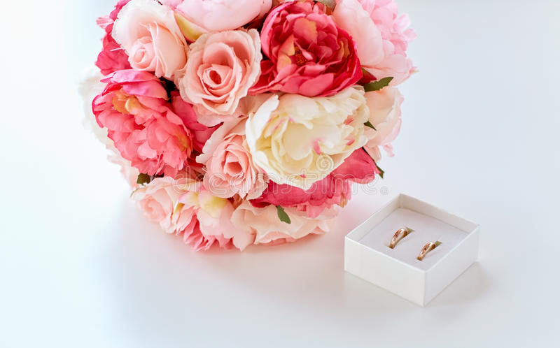 Close up of gay wedding rings and flower bunch. People, homosexuality, same-sex marriage and love concept - close up of gay female wedding rings in little box royalty free stock image