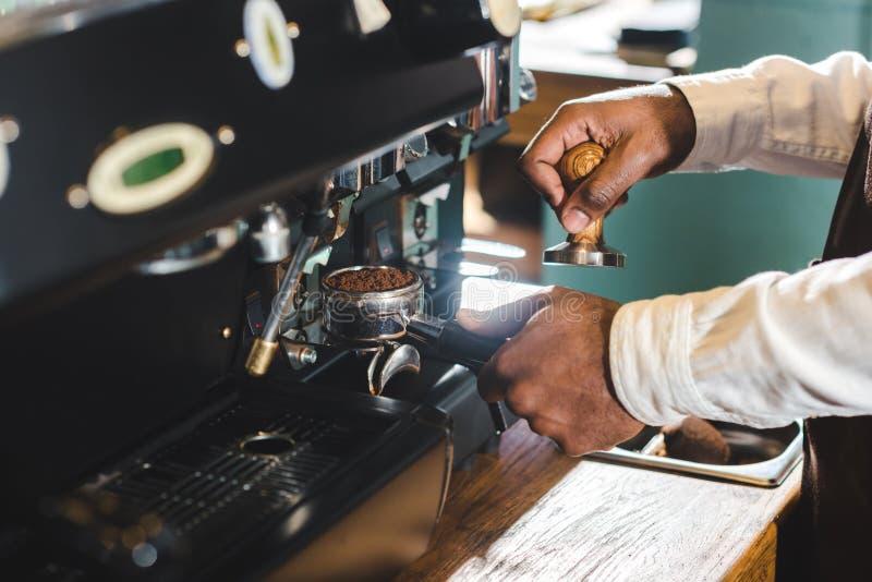 close-up gedeeltelijke mening die van Afrikaanse Amerikaanse barista in schort koffie maken stock fotografie