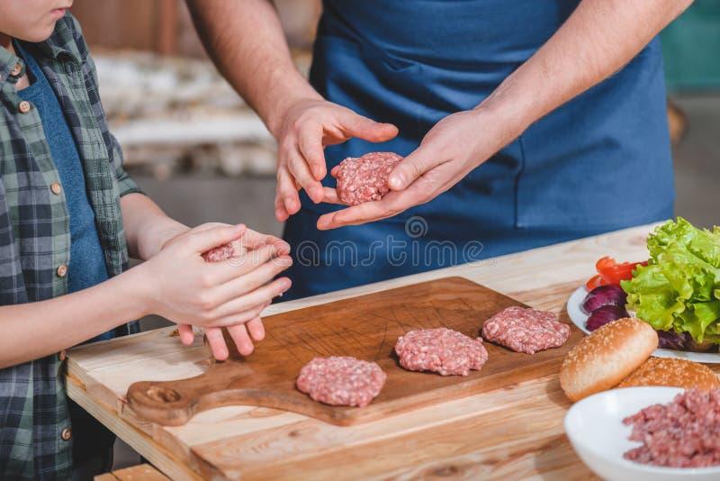 Close-up gedeeltelijke mening van vader en zoons het koken burgers op houten scherpe raad stock fotografie