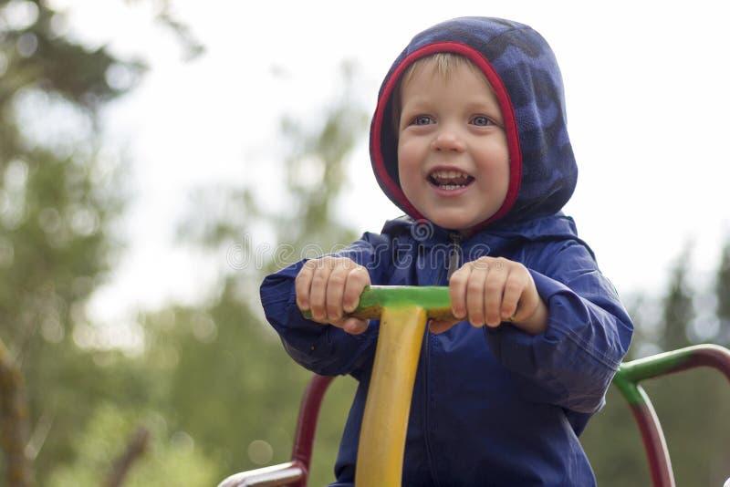 Close-up gelukkig jong geitje met het stuk speelgoed van de het spelcarrousel van het glimlachgezicht op de speelplaatsachtergron royalty-vrije stock foto