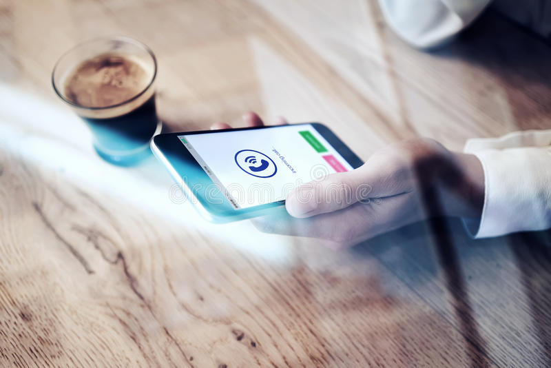 Close up of generic design smartphone with incoming call icons holding in female hand. Cup espresso on the wood table royalty free stock photo