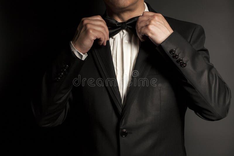 Close-up of gentleman wearing black tie straightens his bowtie. stock photos