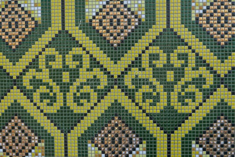 Close up of geometric and floral pattern of green,yellow,brown and white ceramic tiles royalty free stock photography
