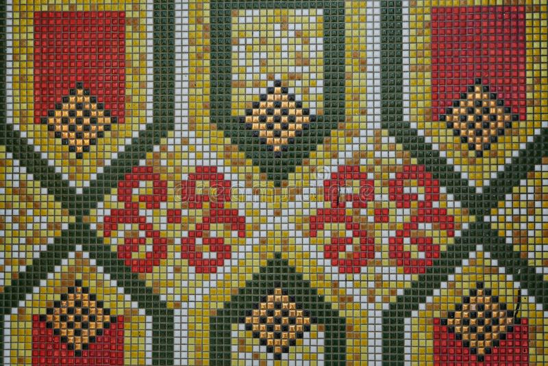 Close up of geometric and floral pattern of green,yellow,red and white ceramic tiles stock photo