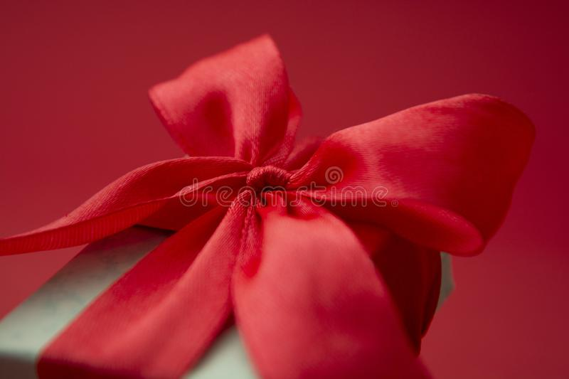 Close up gift box, birtday gift with red bow on red background. Love, Valentine's Day, Mother's Day. Close up gift box, birtday gift with red bow on stock photography