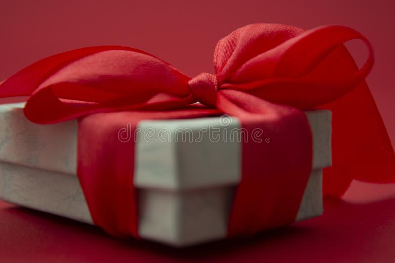 Close up gift box, birtday gift with red bow on red background. Love, Valentine& x27;s Day, Mother& x27;s Day. Close up gift box, birtday gift with red bow on stock photos