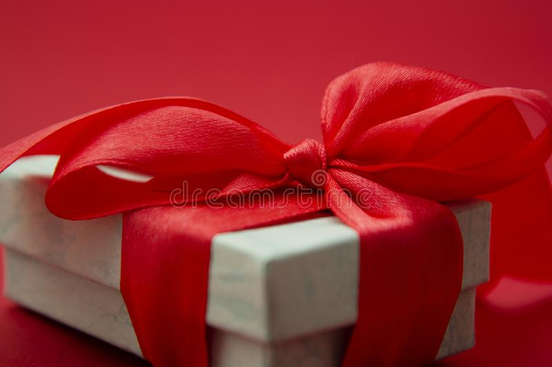 Close up gift box, birtday gift with red bow on red background. Love, Valentine& x27;s Day, Mother& x27;s Day. Close up gift box, birtday gift with red bow on stock images