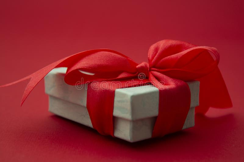 Close up gift box, birtday gift with red bow on red background. Love, Valentine's Day, Mother's Day. Close up gift box, birtday gift with red bow on stock image