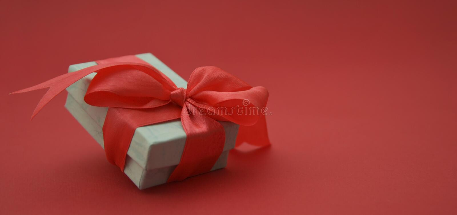 Close up gift box, birtday gift with red bow on red background. Love, Valentine& x27;s Day, Mother& x27;s Day. Banner. Close up gift box, birtday gift with red stock images
