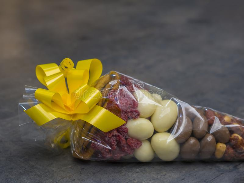 Close up gift cellophane cone full of luxury dried fruit chocholate nuts with yelow topknot on grey decorative background royalty free stock photos