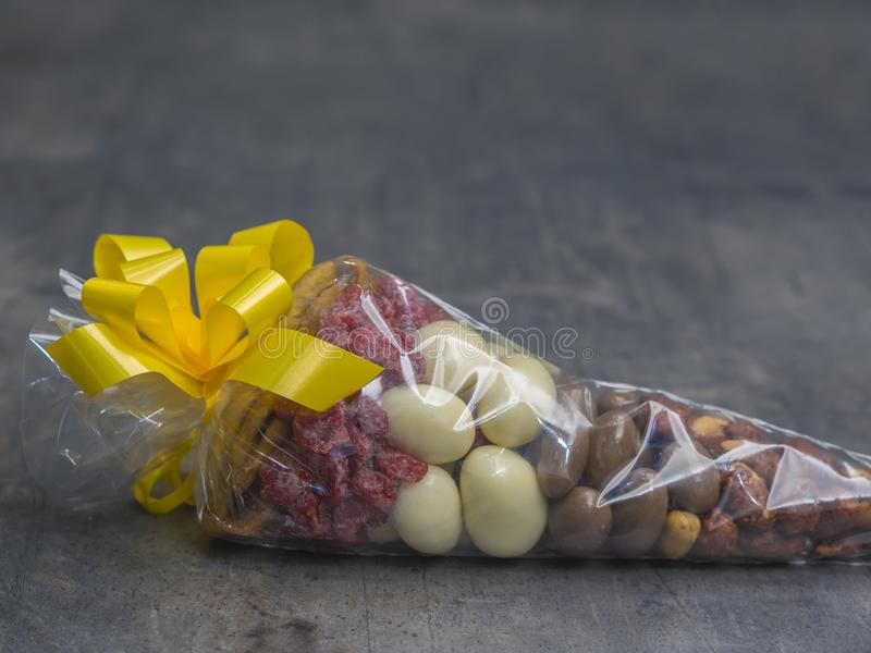Close up gift cellophane cone full of luxury dried fruit chocholate nuts with yelow topknot on grey decorative background stock image