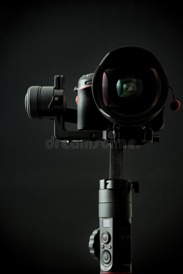 Close-up of gimbal stabilizer, and dsl camera with a black background. Close-up of gimbal stabilizer, and dsl camera with low-key lighting and a black background stock photo