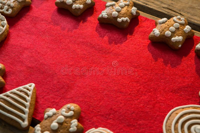 Close up of gingerbread cookies arranged on fabric. Close up of gingerbread cookies arranged on red fabric at table stock image