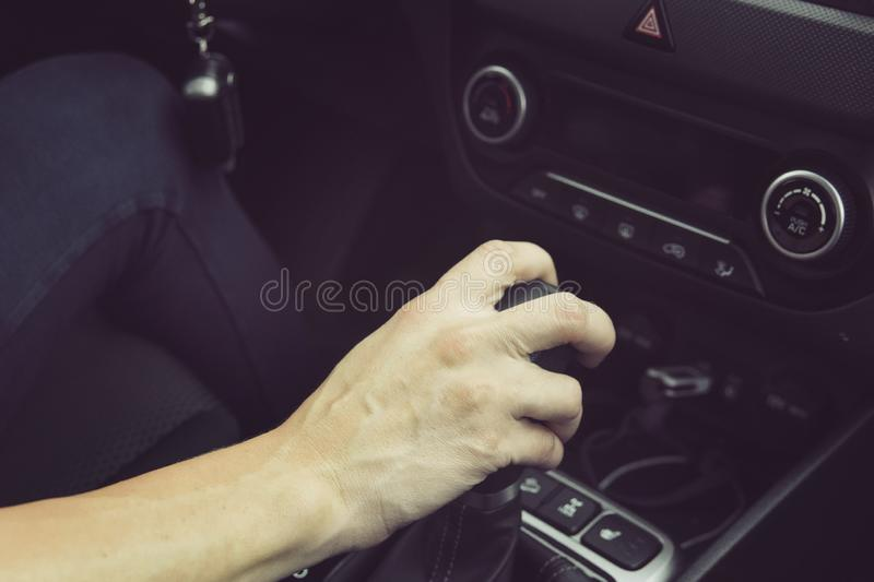 Close up of girl driving car moving transmission shift gear. Concept of female driving car. Using vehicle with modern automatic. Gearbox. Moment of shifting stock image