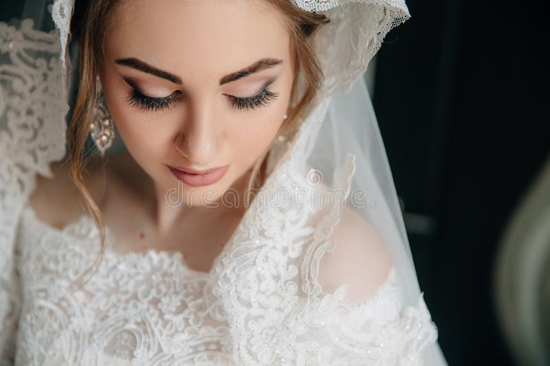 Close-up of a girl face that looks down. Beautiful natural make-up of eyes, long thick eyelashes, white large earrings royalty free stock photography