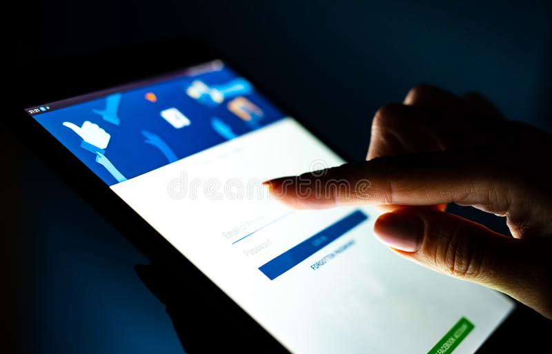 Close up girl hand using tablet with Facebook app royalty free stock image