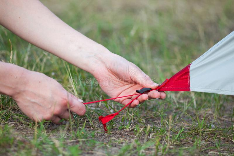 Close-up of Girl hands fastens a tent for camping pegs. royalty free stock photos