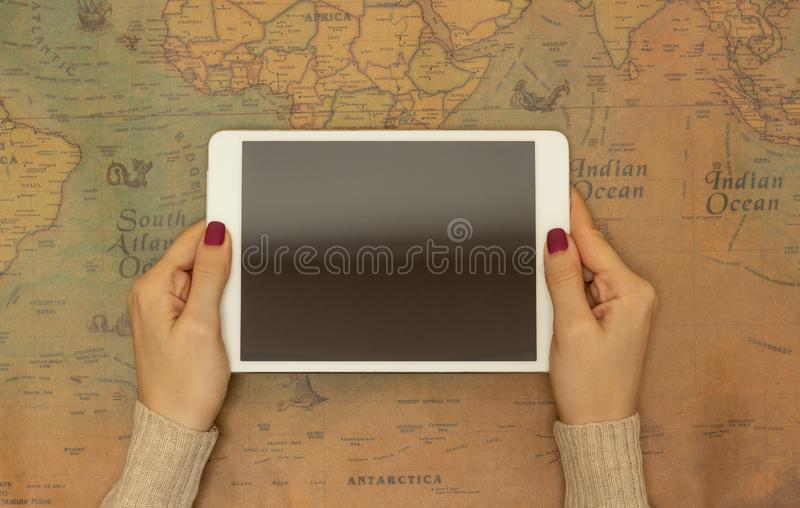 Close-up, girl holding a tablet on the background of a world map, the concept of finding a country for travel stock photography