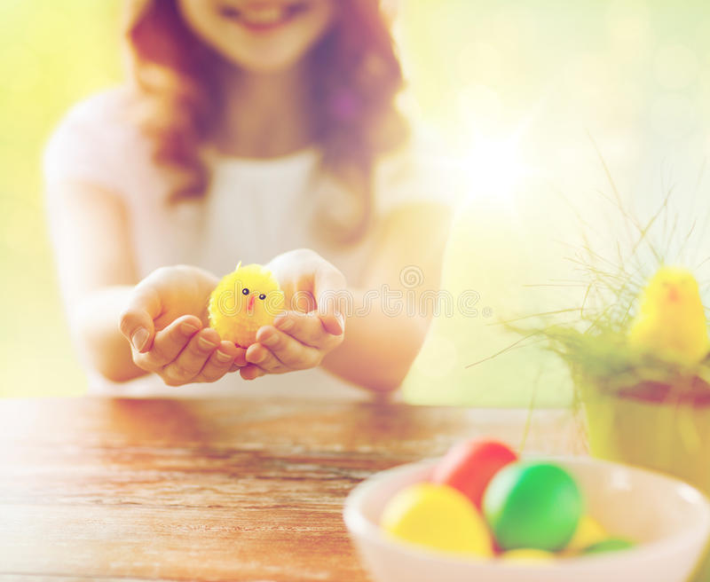 Close up of girl holding yellow chicken toy. Easter, holidays and people concept - close up of girl holding yellow chicken toy and colored eggs on table royalty free stock images