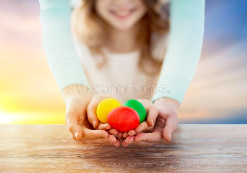 Close up of girl and mother holding easter eggs stock image