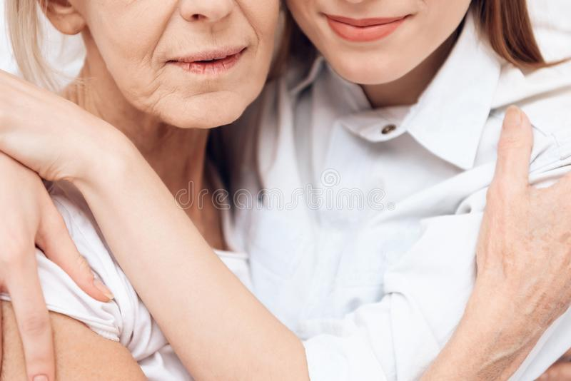 Close up. Girl is nursing elderly woman at home. They are hugging each other. stock images