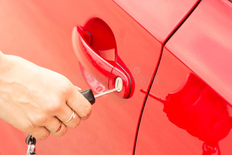 Close-up, the girl opens the door of a red car stock image