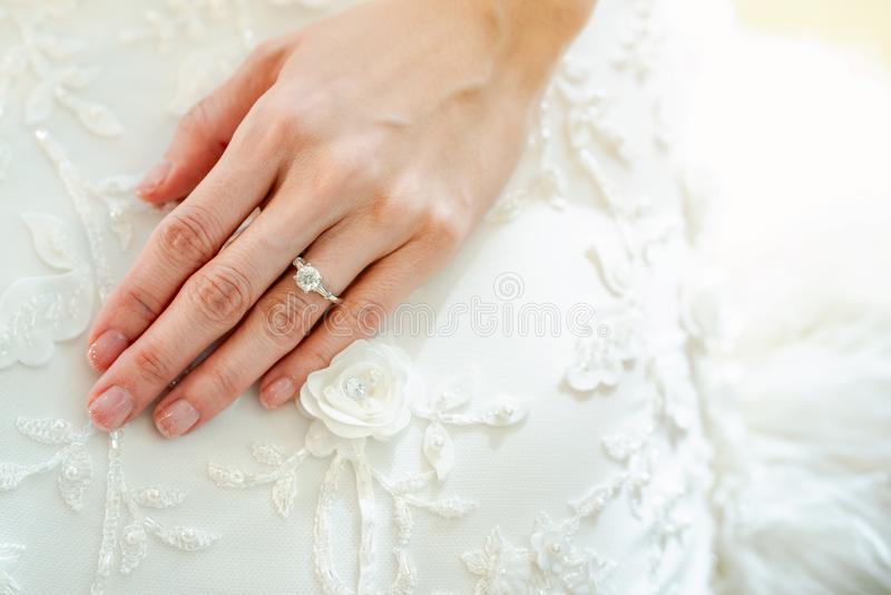 The close-up of the girl`s hand is wearing a ring on the left ring finger. Put your hands on the white bridal gown stock photos