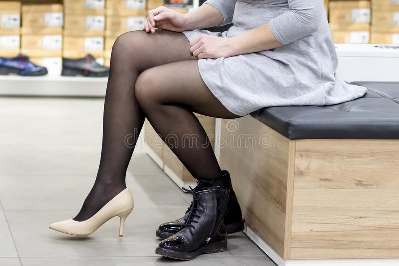 Close-up of girl trying on new fashion shoes in shoe store. young woman dresses gorgeous shoes in boutique of fashionable shoes stock photo