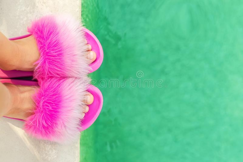 Close-up girl or woman feet in glamour fashion fluffy slippers standing on edge of pool with clear turquoise water. Legs wearing royalty free stock photography