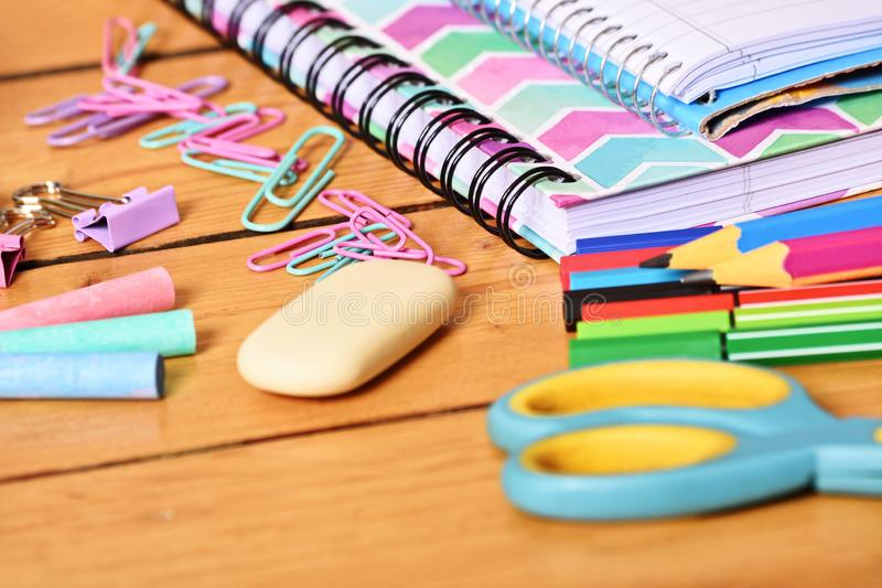 Close up of girly school stationary. Close up shot of pastel colored girl school stationary on wooden background royalty free stock photo