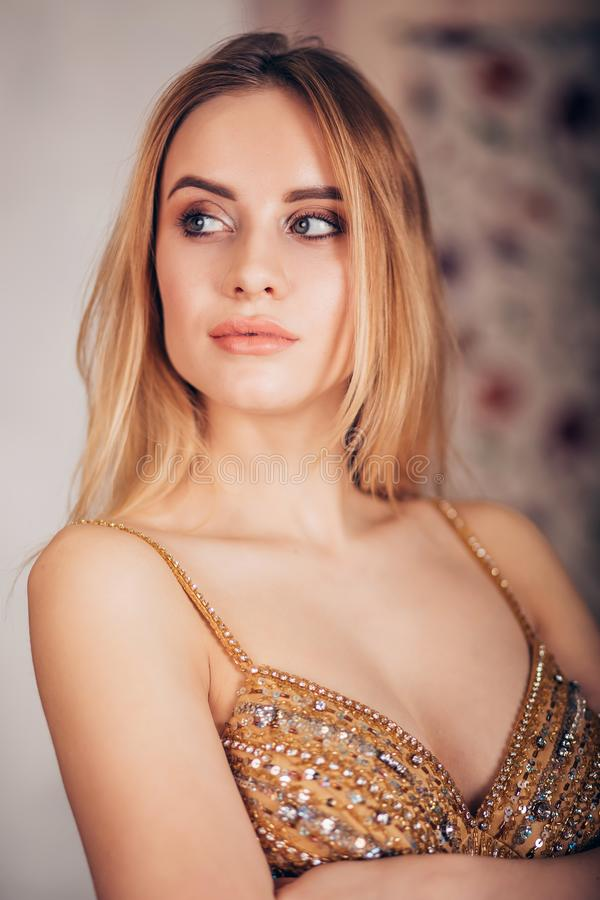 Close-up of glamorous portrait of blonde woman in Golden dress. Beautiful girl looking to the side stock photography