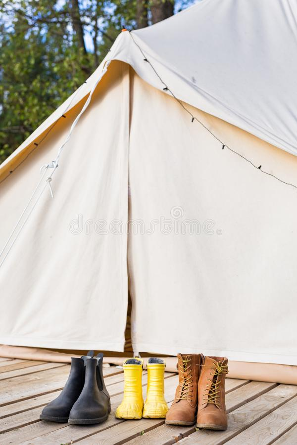 Close-up of glamping bell tent with shoes. Family camping concept stock image