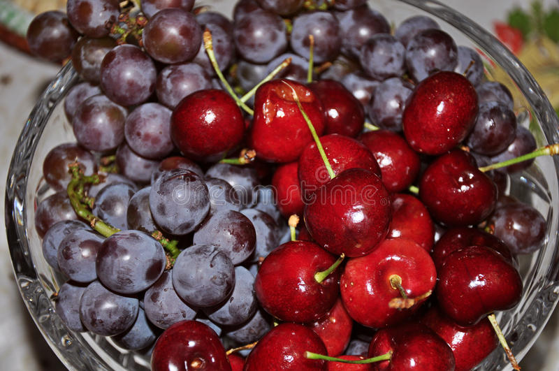 Close-up of glass bowl full of delicious grapes and cherries. royalty free stock photo