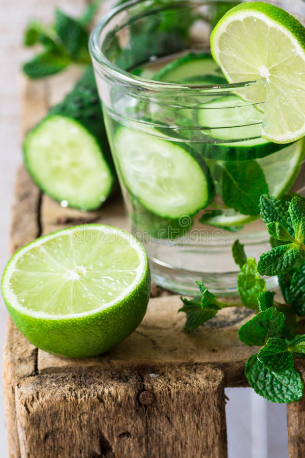 Close up of glass with detox cucumber water with fresh mint and lime on barn wood box, ingredients, spring or summer. Outdoors royalty free stock images