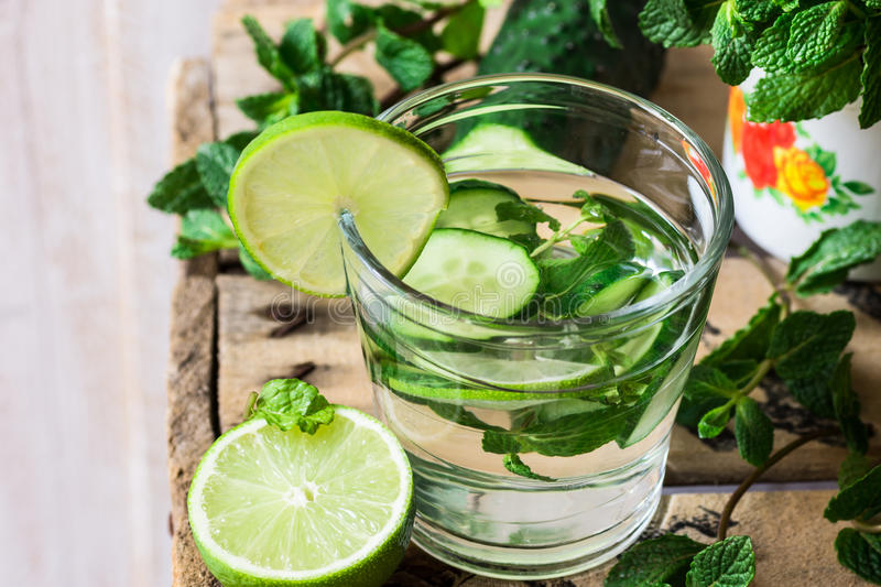 Close up of glass with detox cucumber water with fresh mint and lime on barn wood box, ingredients, spring or summer, outdoors stock photo